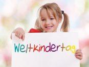 Kind mit Schild zum Weltkindertag