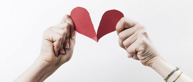 Paar zerreißt rotes Herz